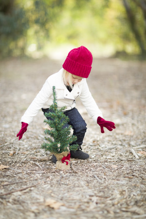 fall winter: Baby Girl In Red Mittens and Cap Near Small Christmas Tree Outdoors. Stock Photo