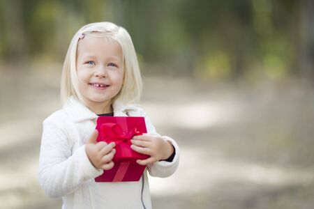 kids outside: Happy Baby Girl Holding Red Christmas Gift Outdoors.