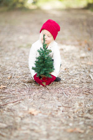 baby near christmas tree: Baby Girl In Red Mittens and Cap Near Small Christmas Tree Outdoors. Stock Photo