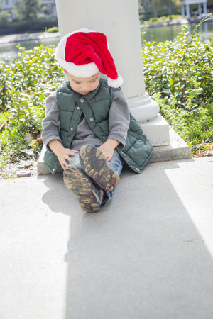 lonely boy: Melancholy Mixed Race Boy Sitting At The Park Wearing Christmas Santa Hat. Stock Photo