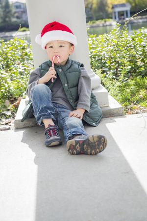 mixed race boy: Cute Mixed Race Boy Sitting Wearing Christmas Santa Hat and Enjoying A Candy Cane. Stock Photo