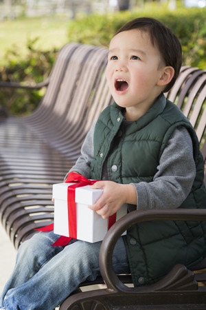 mixed race boy: Adorable Mixed Race Boy Opening A Christmas Gift Outdoors On A Bench.