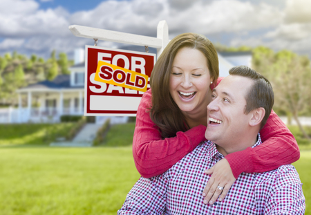 real estate sold: Happy Laughing Couple In Front of Sold For Sale Real Estate Sign and Beautiful House. Stock Photo
