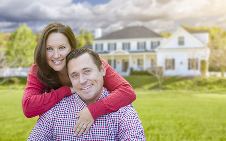 new homes: Happy Affectionate Couple Outdoors In Front of Beautiful House. Stock Photo