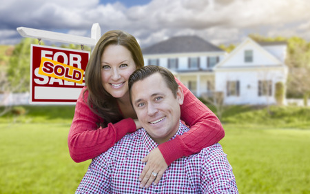 sign in: Happy Couple In Front of Sold For Sale Real Estate Sign and Beautiful House.