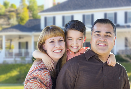 Happy Mixed Race Young Family in Front of Beautiful House. Banque d'images