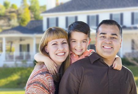 niños latinos: Feliz de la raza mezclada joven de la familia en frente de casa hermosa.