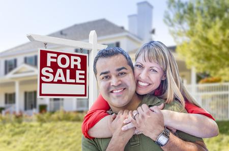 mixed race couple: Happy Mixed Race Couple in Front of For Sale Real Estate Sign and New House. Stock Photo