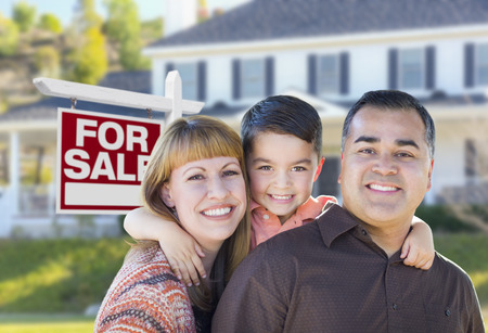 Happy Young Mixed Race Family in Front of For Sale Real Estate Sign and New House.