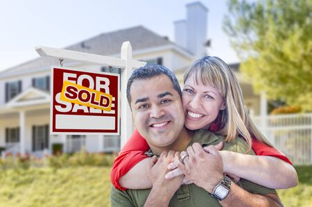home sale: Happy Mixed Race Couple in Front of Sold Home For Sale Real Estate Sign and House. Stock Photo