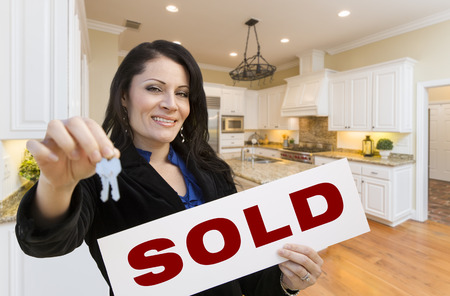 sold sign: Pretty Hispanic Woman In Kitchen Holding House Keys and Sold Sign.