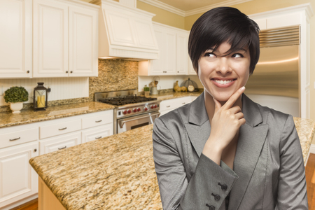 designer: Pretty Mixed Race Woman Looking Back Over Shoulder Inside Custom Kitchen Interior. Stock Photo