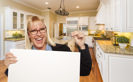 blank sign: Happy Young Woman Holding Blank Sign and Keys Inside Beautiful Custom Kitchen.