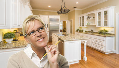 custom: Attractive Daydreaming Woman with Pencil Inside Beautiful Custom Kitchen. Stock Photo