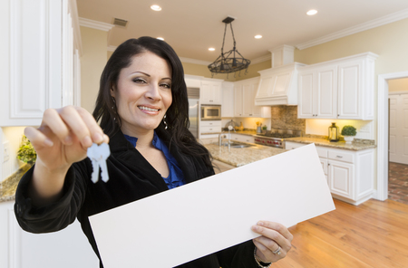 room for text: Pretty Hispanic Woman In Kitchen Holding House Keys and Blank White Sign.