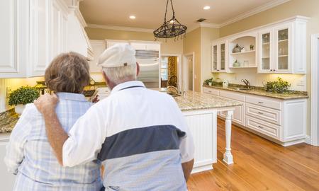 adult 80s: Happy Senior Couple Looking Over Beautiful Custom Kitchen Design.