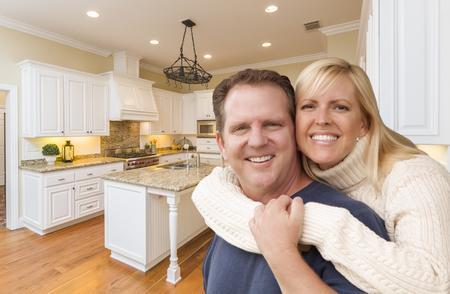 Happy Couple Hugging Inside Beautiful Custom Kitchen. Reklamní fotografie