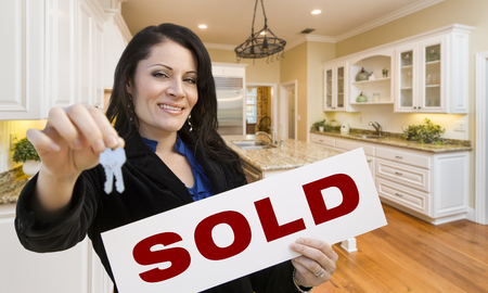 homebuyer: Pretty Hispanic Woman In Kitchen Holding House Keys and Sold Sign.