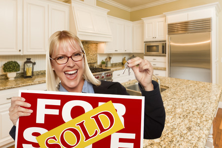 real estate sold: Happy Young Woman Holding Sold For Sale Real Estate Sign and Keys Inside Beautiful Custom Kitchen.