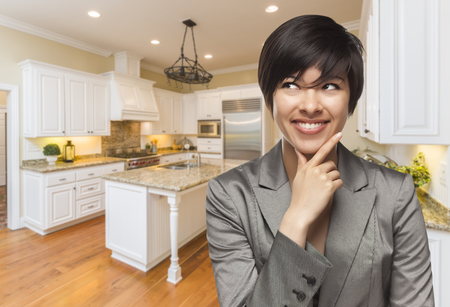 Pretty Mixed Race Woman Looking Back Over Shoulder Inside Custom Kitchen Interior. photo
