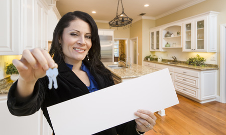 homebuyer: Pretty Hispanic Woman In Kitchen Holding House Keys and Blank White Sign.
