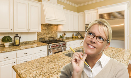 daydreaming: Attractive Daydreaming Woman with Pencil Inside Beautiful Custom Kitchen. Stock Photo