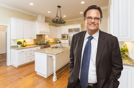 kitchen remodelling: Handsome Man Wearing Suit and Tie in Beautiful Custom Residential Kitchen.