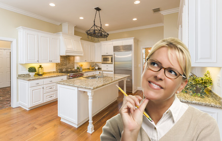 Attractive Daydreaming Woman with Pencil Inside Beautiful Custom Kitchen. Stock Photo