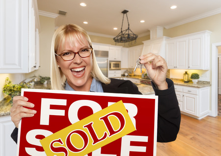 real estate sign: Happy Young Woman Holding Sold For Sale Real Estate Sign and Keys Inside Beautiful Custom Kitchen.