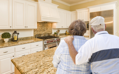 inside: Happy Senior Couple Looking Over Beautiful Custom Kitchen Design.