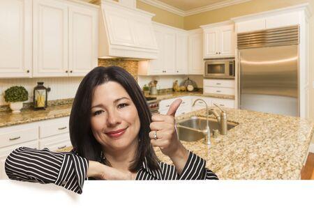 Spaanse vrouw met Thumbs Up In Custom Kitchen Interior Scheve op wit.