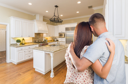 kitchen remodelling: Young Hopeful Military Couple Looking At Beautiful Custom Kitchen.