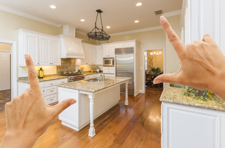 framing: Female Hands Framing A Beautiful Custom Kitchen Interior.