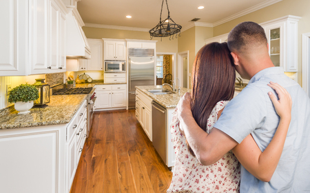 real estate: Young Hopeful Military Couple Looking At Beautiful Custom Kitchen.