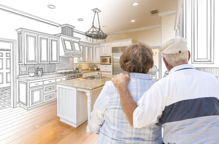 senior couple: Senior Couple Looking Over Custom Kitchen Design Drawing and Photo Combination.