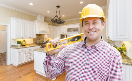 tools construction: Smiling Contractor with Level Wearing Hard Hat Standing In Custom Kitchen.