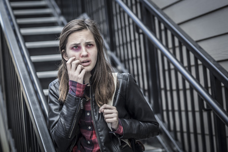 molestation: Young Badly Bruised and Frightened Girl with Backpack on Staircase.