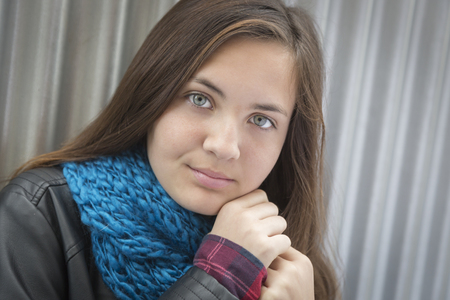 Portrait of Young Pretty Blue Eyed Girl Against Metal Backdrop.