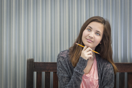 teenaged girls: Pretty Young Daydreaming Female Student With Pencil Sitting on Bench Looking to the Side. Stock Photo