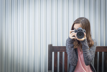 teenaged girls: Girl Photographer Sitting On Bench and Pointing Camera.