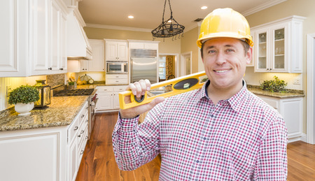 person: Smiling Contractor with Level Wearing Hard Hat Standing In Custom Kitchen.