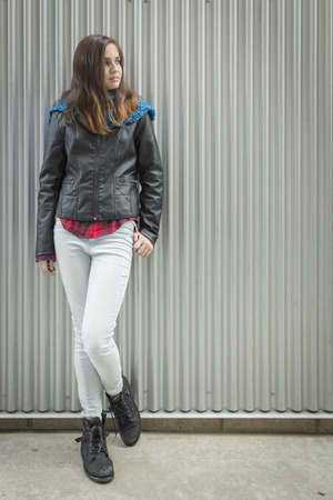 Young Teen Girl Wearing Leather Jacket Standing Against Metal Wall and Looking to the Side.
