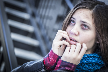 teenaged girls: Young Badly Bruised and Frightened Girl on Staircase. Stock Photo