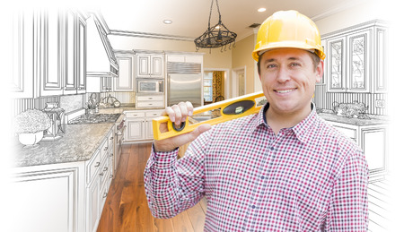 builder: Smiling Contractor in Hard Hat with Level Over Custom Kitchen Drawing and Photo Combination. Stock Photo