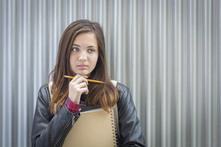 teenaged: Pretty Young Melancholy Female Student With Books and Pencil Looking to the Side. Stock Photo