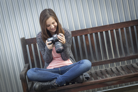 text space: Young Girl Photographer Sitting on Bench Looking at Back of Camera. Stock Photo
