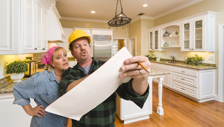 inside house: Male Contractor in Hard Hat Discussing Plans with Woman in Custom Kitchen Interior.