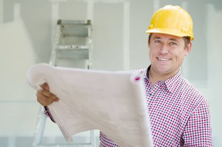 property ladder: Smiling Contractor Holding Blueprints Inside Home Construction Site. Stock Photo