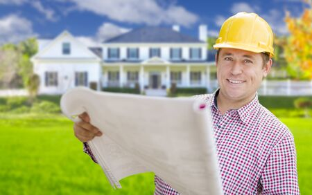 custom home: Smiling Contractor Holding Blueprints In Front of  Beautiful Custom Home.