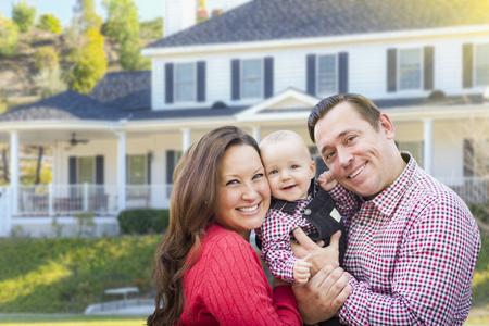 Esposas: Familia joven feliz con el bebé al aire libre delante de bellas vivienda personalizado.